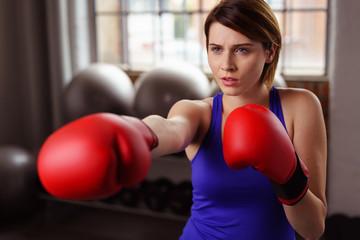 frau mit boxhandschuhen im fitnessstudio