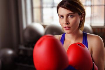 frau mit roten boxhandschuhen im fitness-club