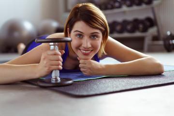 frau liegt im fitnessstudio auf einer matte mit einer kurzhantel