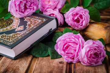 Quran and pink roses on wooden background. Selective focus