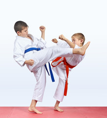 Two karateka children are beating kick leg