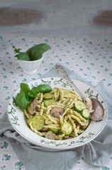 Typical genoa Pesto, Pasta Trofie with pesto, mushrooms and zucchini. Vegetarian dishes. Italian traditional cuisine food, recipes.