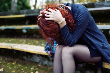 Ginger woman sitting in despair on the bench in the park, head in the hands