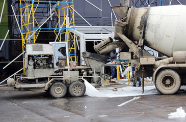 concrete pump and  mixer to work together  pouring cement floors in the shopping center for repair.