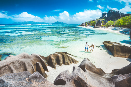 A young couple standing in shallow water on La Digue island, Sey