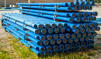 Stacks of blue PVC water pipes  in stack on open storage at an factory