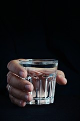 Glass of water in the hand on the dark background. Creative shot