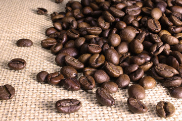 Brown coffee grains scattered on a sack textile.