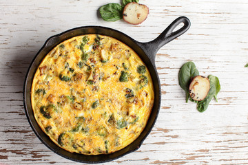 Baked egg frittata with spinach, cheese, broccoli, red potatoes, bacon, milk, and spinach far away shot from top