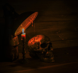 still life with skull and candle with candlestick
