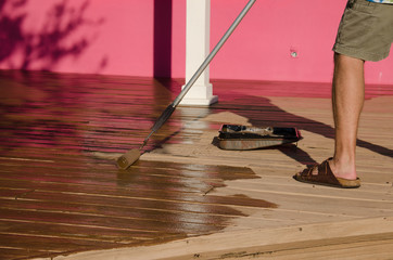 A DIY do-it-yourself home owner is staining painting a house wooden deck with a long handle paint roller on a sunny day.