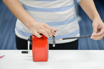Woman is sharpening the pencil with red sharpener