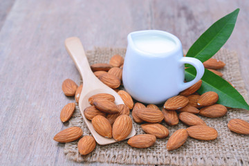 Almond milk in white mug with almond nuts on wooden spoon and table.