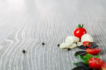 Cherry tomatoes, garlic and fresh basil on grey wooden  background. Frame. Copy space.