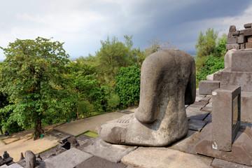 The damaged Buddha statue at Borobudur temple , the 9th century Buddhist temple in Magelang Regency near Yogyakarta, Java Island, Indonesia