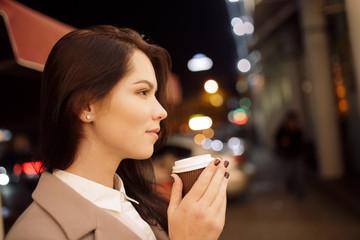 Woman enjoying aroma coffee in night city