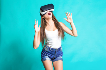 Sexy young girl with glasses of virtual reality on a blue background.