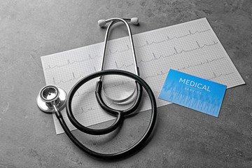 Medical service concept. Visiting card, cardiogram and stethoscope on grey background