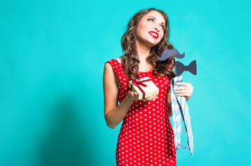 Funny girl in a red dress holding a mustache Photo Booth support for the concept of humor.