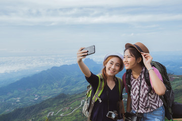 Asian tourists are enjoying the selfie with friends. They have c