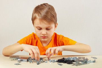 Little boy plays with mechanical kit at the table