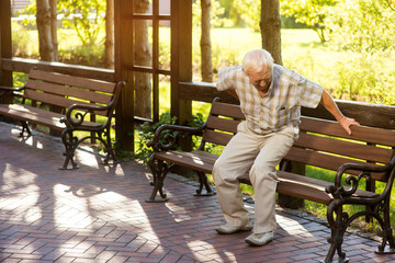 Senior man holding his back. Old male near park bench. Strong pains in spine. Need of medication and therapy.