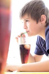 Garçon buvant un soda à la paille