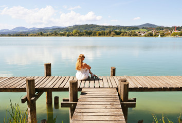 Girl on the wooden jetty at the lake. Switzerland