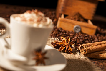 Close-up on star anise and cinnamon sticks with coffee cup