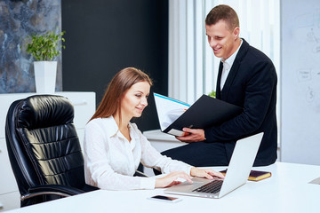 Happy executive or secretary giving documents to a businessman i