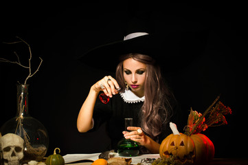 Witch in the hat at the table. Mixes the potions. On a black background.