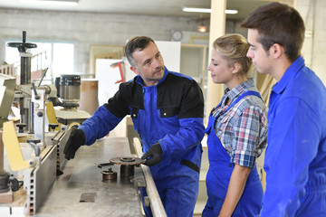 Professional teacher showing carpentry machinery to students
