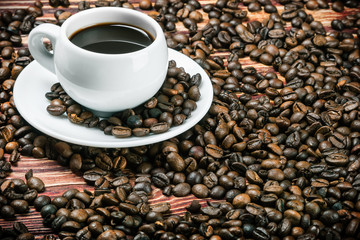 roasted coffee beans and a cup of prepared beverage