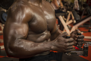 Hunky muscular black bodybuilder working out in gym, exercising back on machine