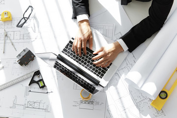 Top shot of architect or contractor sitting at desk with laptop computer, sketches, scale model house, blueprint rolls and ruler, entering data while working on new housing project in his office