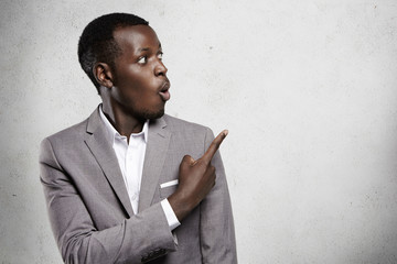 Attractive astonished bug-eyed dark-skinned businessman or office worker in formal wear looking away at blank wall in surprise, pointing his finger at copy space for your text or advertising content