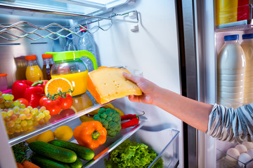 Woman takes the piece of cheese from the open refrigerator