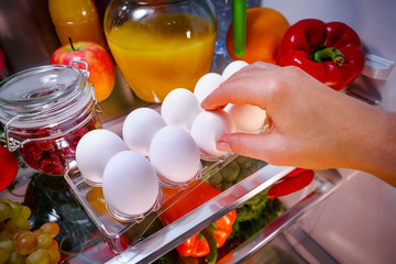 Chicken eggs on a shelf open refrigerator