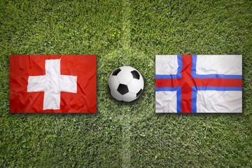 Switzerland vs. Faroe islands flags on soccer field