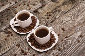 two small white cups of coffee with cocoa beans on wooden background