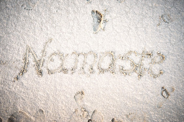 Hand drawn Namaste lettering on sand.