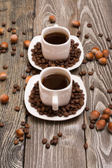 two small white cups of coffee with cocoa beans, slices of chocolate and hazelnuts on wooden background