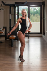 Pretty Woman Flexing Muscles In Gym
