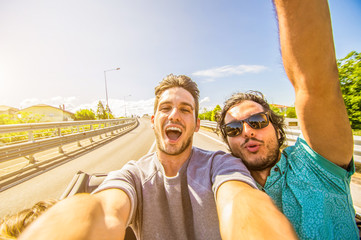 Happy friends taking selfie at car trip around Europe.