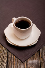 small white cup of coffee on grey fabric on wooden background