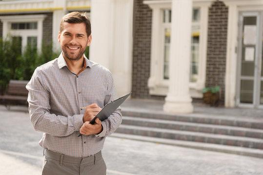 Smiling realtor standing outside modern house