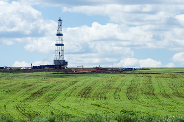Oil rig in the middle of the field. Spring