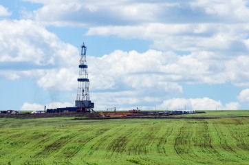 Oil rig among green fields. Spring