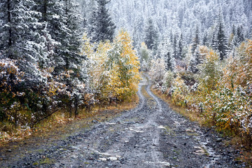 First autumn snow and rural road in mountains