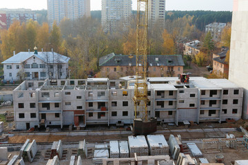 Construction site with crane and part of concrete slabs building